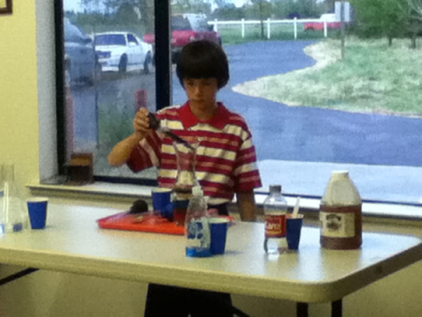 Davey--filling a jar with different household substances to demonstrate the layers of the atmosphere.